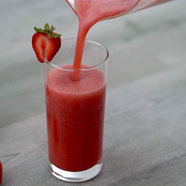 pouring strawberry juice in serving glass