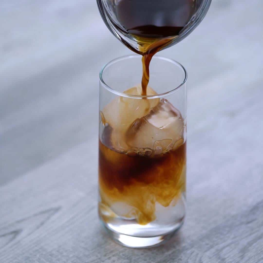 Pouring cold brew coffee over ice in to glass
